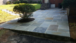 Pennsylvania flagstone patio in backyard with cut out for shrubbery