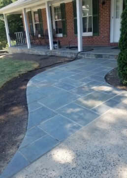 Flagstone walkway leading up to porch made out of flagstone