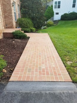 Brick walkway in front yard leading to house