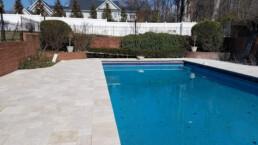 Backyard pool and pool deck made of travertine stone
